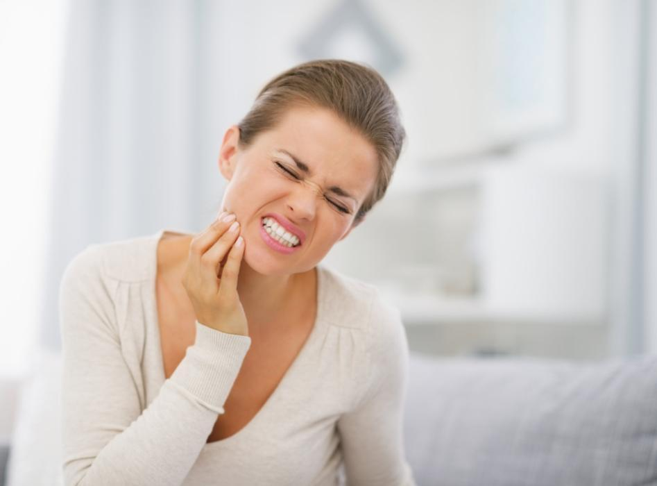 woman holding jaw from pain | Dentist Vallejo CA